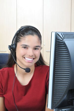 Smiling receptionist at computer talking on headset Stock Photo - 4294771