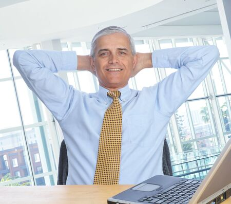 Businessman Siting at His Desk with hands behind his head Stock Photo - 4449006