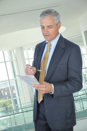 Businessman in office building reading newspaper photo