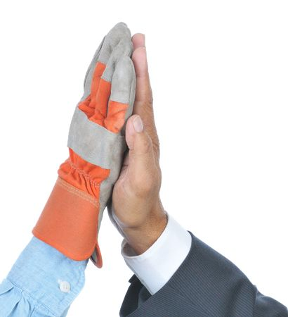 Two hands doing a High Five one in business attire the other in Laborer work glove and shirt Stock Photo
