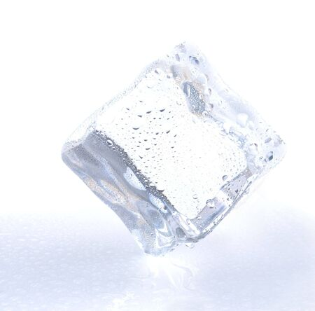 Ice cube balanced on one corner melting on reflective surface with water droplets with cool blue tones