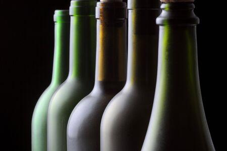 Close-up van Vijf wijnflessen op zwarte achtergrond