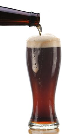 Glass of Dark Ale Beer being Poured from Bottle with Foam Drip and Reflection isolated on white photo