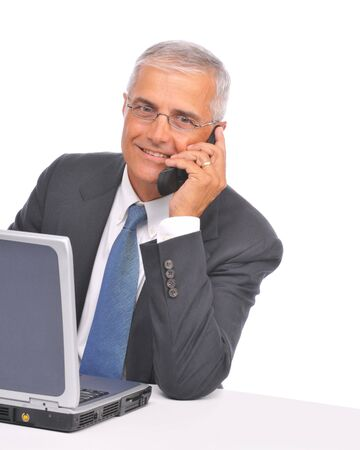 Mature Businessman seated at desk with laptop talking on cell phone isolated on white photo