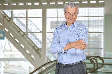 Smiling Businessman Standing Indoors in front of Escalator With Arms Crossed  photo