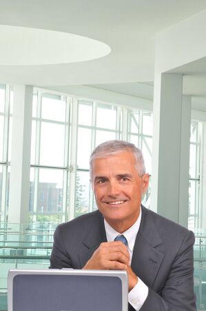 Smiling Mature Businessman Lookong over top of Laptop Computer in office setting - hands clasped photo