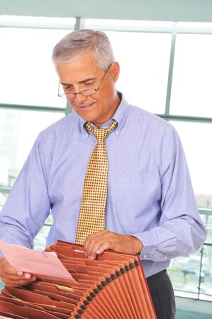 filing: Businessman Putting Papers in File Box in front of Office Window
