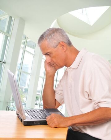 Man Looking Intently at Laptop side view in office setting photo