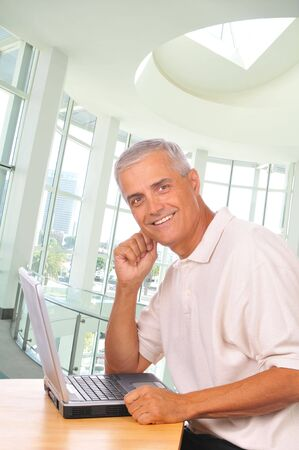Smiling Mature Businessman Seated at Computer seen from the side in Office Setting photo