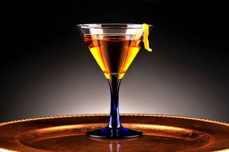 barware: Whiskey Drink and Lemon Twist with light to dark spot lit background. Horizontal Composition
