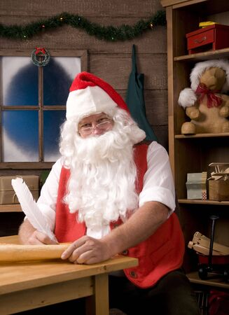 Santa Claus Sitting in His Workshop with Quill Pen Writing on His List. Vertical Composition.