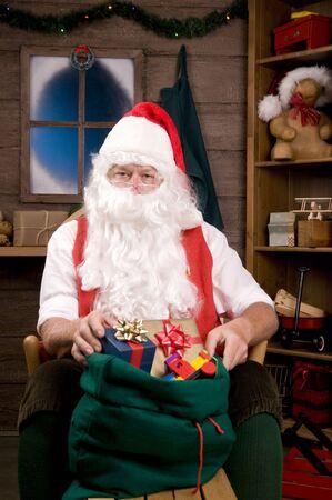 composition vertical: Santa Claus seduta � una sedia a dondolo con regali e giocattoli in Borsa. Composizione verticale - concentrarsi su Santa