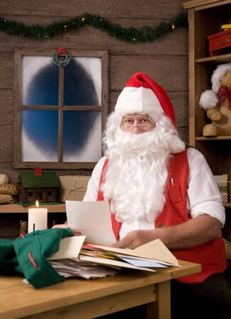 vertical composition: Santa Claus Sitting in His Workshop Painting reading letters. Vertical Composition.