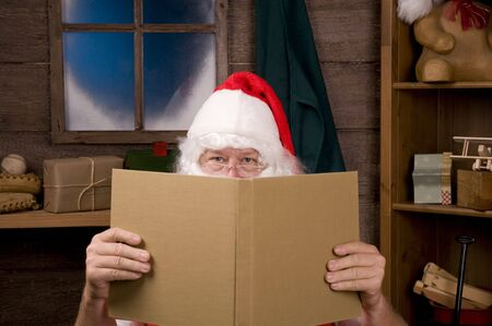 composition book: Santa Claus Sitting in His Workshop peering over the top of a large book. Horizontal Composition - Focus on Santas eyes, slight reflection in window.