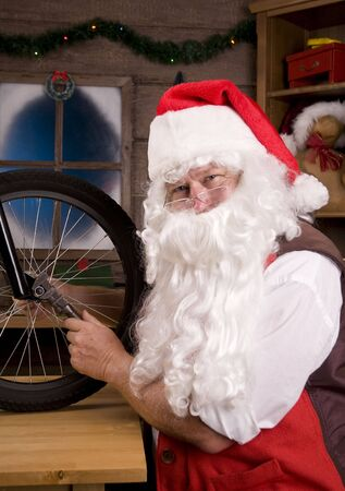 st  nick: Santa Claus Assemblying a Bicycle in His Workshop. Vertical Composition, closeup of Santa using wrench on Bike wheel. Stock Photo