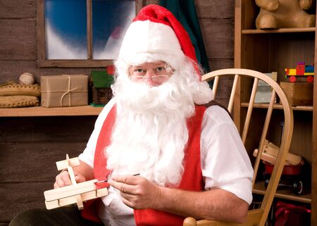 Santa Claus sitting in Rocking Chair in his workshop painting a toy airplane. Horizontal composition. photo