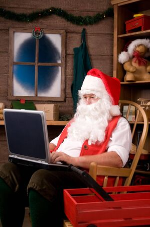 Santa Claus Sitting in Rocking Chair in Workshop Using Laptop. Vertical composition.