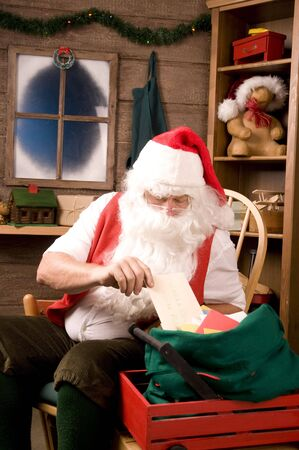 vertical composition: Santa Claus Sitting in His Workshop taking a letter from a mailbag. Vertical Composition. Stock Photo