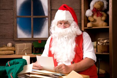 Santa Claus Sitting in His Workshop reading a letter. Horizontal  Composition. photo