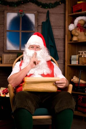 st nick: Santa Claus in Rocking Chair with Naughty List Going Shh. Vertical Composition
