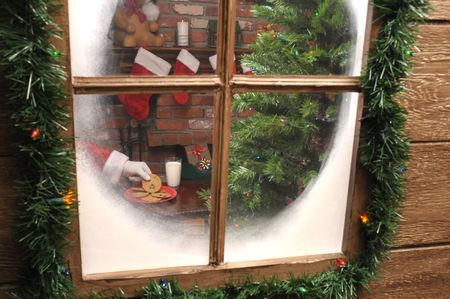 fireplace: Looking Through the  window of a house as Santa Claus takes a cookie and and glass of milk.