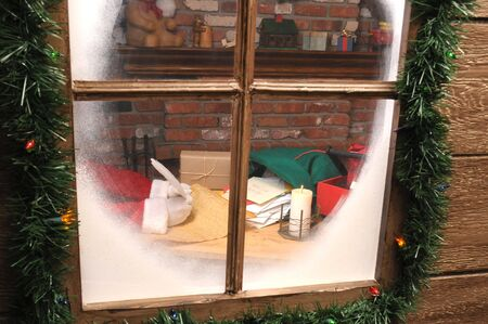 Looking through window at Santa Claus in Workshop With Quill Pen and Naughty List and sack of letters. Santas hands only.
