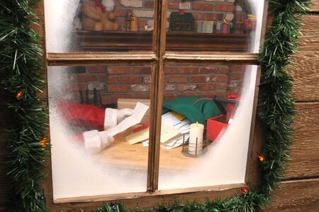 st  nick: Santa Claus Sitting in His Workshop reading a letter seen through window. horizontal Composition. Stock Photo