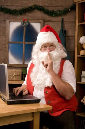 traditional gifts: Santa Claus in Workshop Using Laptop and making Shh sigh at viewer. Vertical Composition