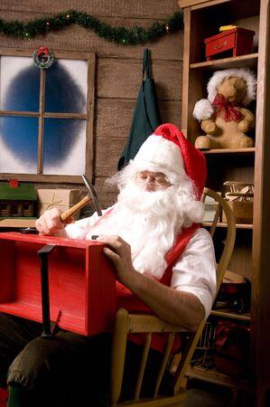 composition vertical: Santa Claus seduta in Rocking Chair in Workshop con Red Wagon di legno sulle ginocchia, Vertical Composition Archivio Fotografico