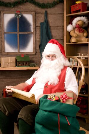 st  nick: Santa Claus in Rocking Chair with Naughty List and Bag of Toys, vertical composition