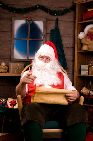 Santa Claus in Rocking Chair with Naughty List and Pointing at Viewer. Vertical Composition photo