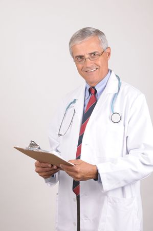 50 yrs: Portrait of a Mature Male Doctor in Lab Coat with Stethoscope and Clip Board, Vertical Composition on Gray Background