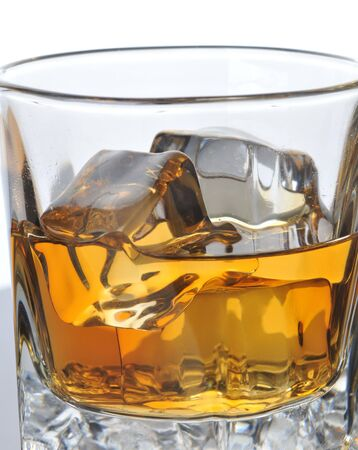 barware: Whiskey in Glass with ice cubes and condensation, close up with white background