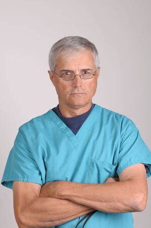 50 yrs: Mature Doctor in Scrubs with stern expression and his arms folded - vertical on Gray Background