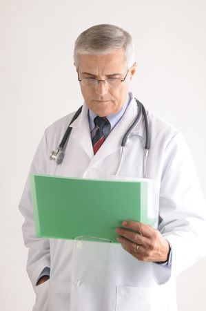 50 yrs: Mature Doctor in Lab Coat and Stethoscope Looking at a Patients Chart Stock Photo