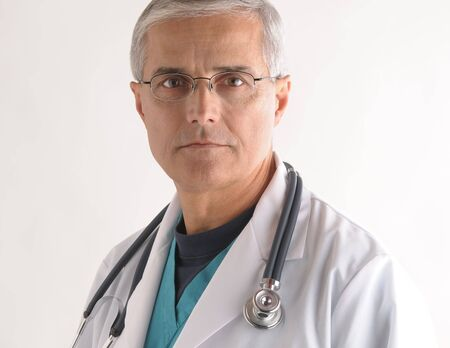 50 yrs: Serious Mature Doctor in Scrubs and Labcoat with Stethoscope closeup Stock Photo