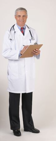 50 yrs: Smiling Mature Male Doctor in Lab Coat with Stethoscope Writing on chart - gray background Stock Photo