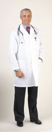50 yrs: Doctor wearing a Lab Coat one hand in pocket full length over gray background vertical format