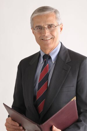 50 yrs: Middle Aged Businessman with Leather Folder over light gray background vertical format