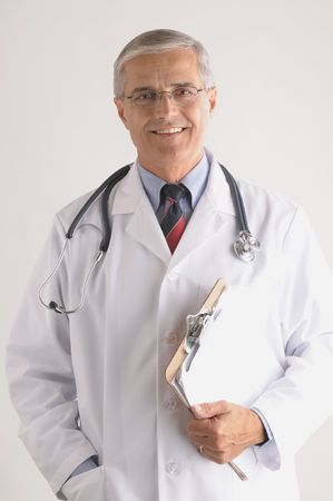50 yrs: Smiling Mature Doctor in Labcoat with Stethoscope and Clip Board Stock Photo