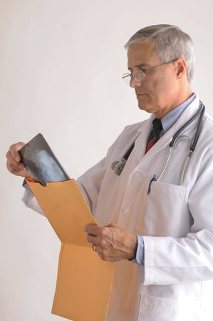 50 yrs: Mature Doctor in Lab Coat Removing an X-Ray from a large envelope