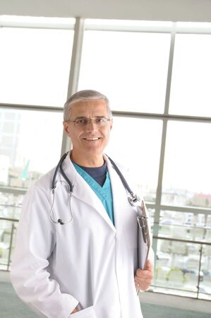 50 yrs: Middle aged doctor with stethoscope and clip board standing in front of large window in modern medical facility