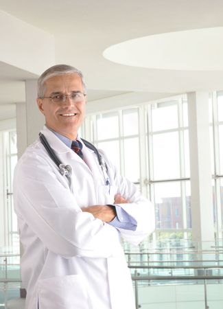 50 yrs: Middle aged doctor wearing lab coat and with arms crossed in modern medical facility Stock Photo