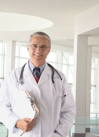 Middle aged doctor wearing lab coat holding a Clip Board in modern medical facility photo