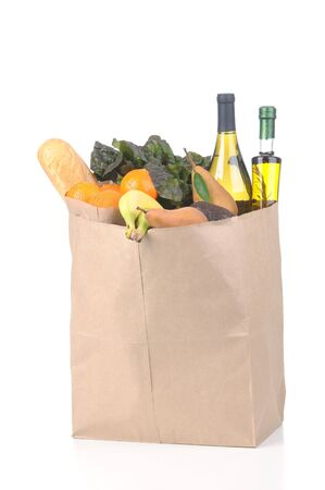 Grocery Bag full of Vegetables Fruit and Wine isolated on white vertical format with reflection photo