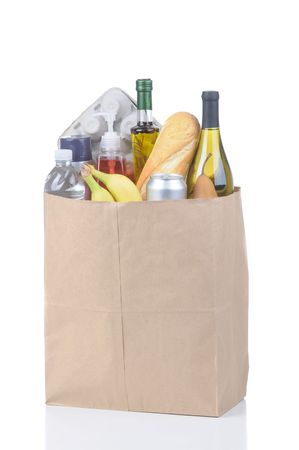 kraft: Brown Kraft Paper Bag full of assorted groceries isolated over white vertical format with reflection Stock Photo