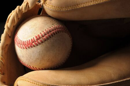 catcher's mitt: Close up shot of a well worn baseball and catchers mitt horizontal format