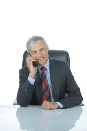 50 yrs: Smiling Middle aged businessman sitting at his desk talking on his cell phone isolated over white with reflection in desk top