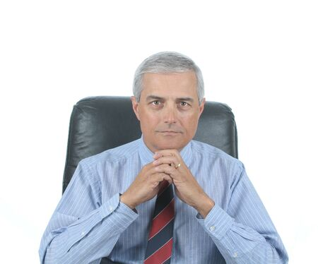 50 yrs: Middle aged businessman sitting at his desk with hands clasped under chin isolated over white