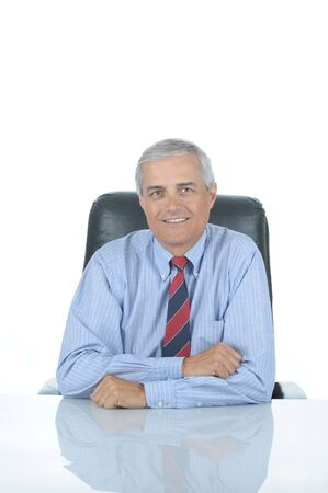 50 yrs: Smiling Middle aged businessman sitting at his desk isolated over white with reflection in desk top